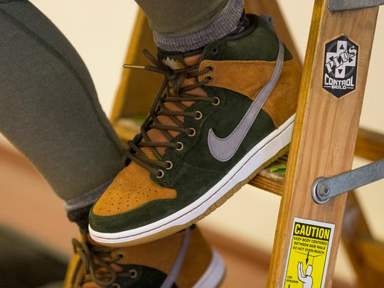Liz Zaharias, of Ithaca, girlfriend of Homegrown store owner Andrew Douglas, watches the initial sales of the  Nike SB Dunk High Premium 'Homegrown'  shoes Friday morning in the store.