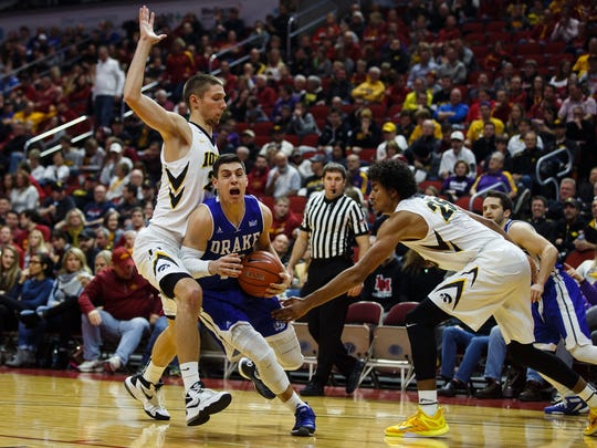 Drake's Reed Timmer drives to the basket between Iowa's Jarrod Uthoff, left, and Dom Uhl during their Big Four Classic game at the Wells Fargo Arena on Saturday, December 19, 2015 in Des Moines.