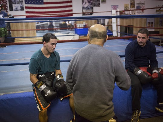 Alfredo Montanez, 33, left, and former professional boxer Eric Nemo, 32, both of York, listen as trainer Julio Alvarez, 65, of Thomasville, center, gives Montanez some advice. Montanez has returned to the ring after spending more than a decade away from the sport. He will make his professional boxing debut Saturday, Jan. 23 at the Hanover Armory.