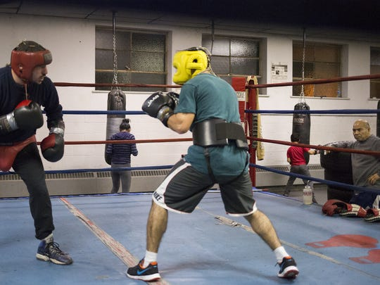 Trainer Julio Alvarez, 65, of Thomasville, far right, watches as former professional boxer Eric Nemo, 32, of York, left, and Alfredo Montanez, 33, of York, spar. Nemo returned to the ring to help Montanez train for his pro debut, scheduled for Saturday, Jan. 23 at the Hanover Armory.