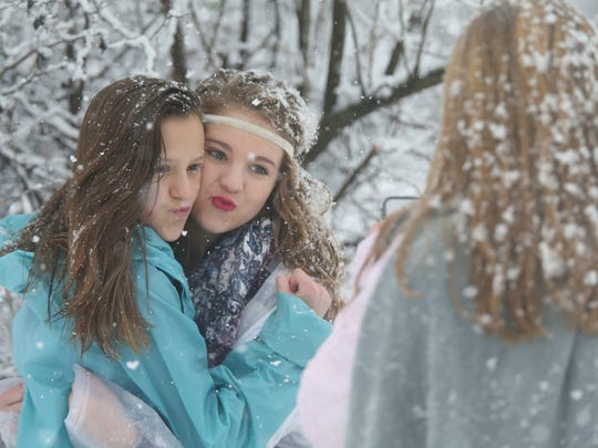 Friends Annabeth Keith, 13, left , and Chloe Frankes, 13, right have their picture taken by Claire Keith, 15, Annabeth's sister, as snow falls on them Friday, Jan. 22, 2016, in Murfreesboro.