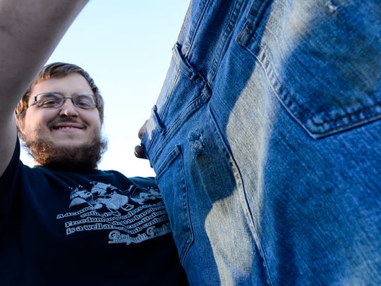 Jeremy Dettinger holds up the jeans he was wearing