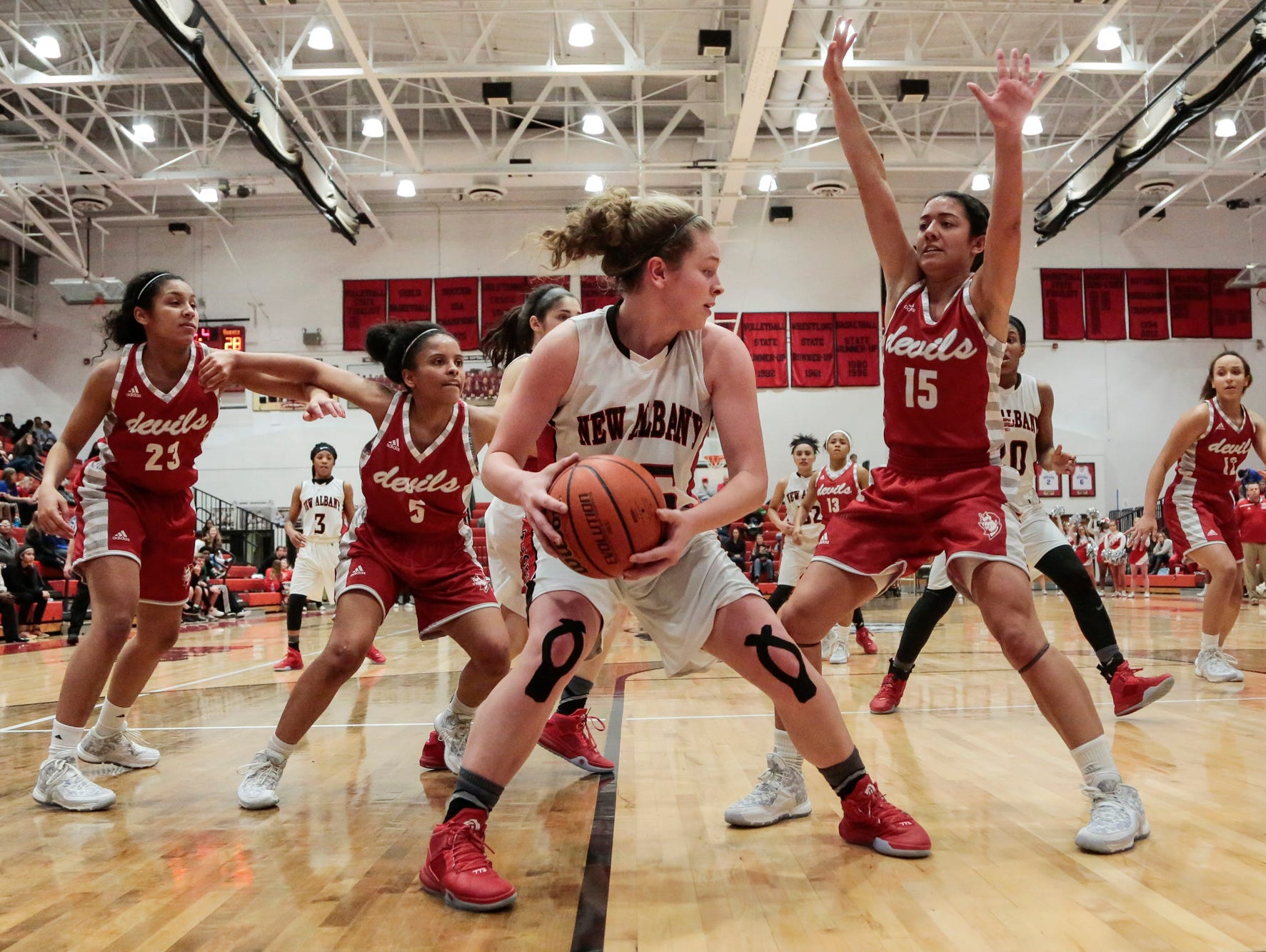 New Albany's Marissa Jones (23) looks to pass while heavily guarded by a swarm of Jeffersonville Devils during the second half of play, Wednesday, Jan. 27, 2016, at New Albany High School in New Albany, In.