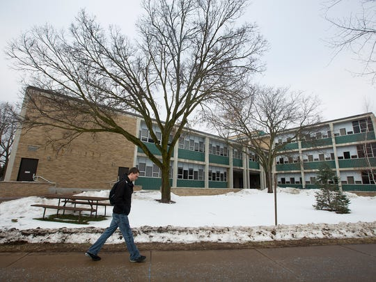 A student walks by the Science Building on the University of Wisconsin - Stevens Point campus, Monday, Feb. 1, 2016.