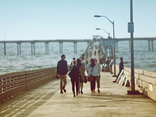This file photo shows people walking on Ocean Beach Pier