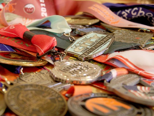 A medal for the Scenic City Trail Marathon in Tennessee is placed among other medals Mike Ball has earned during his running career.