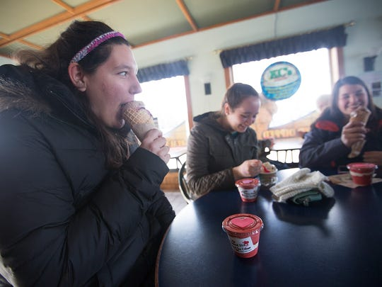 University of Wisconsin - Stevens Point students Cassie Fleege, 21, left, Mallory Jones, 19, center, and Emily Pearson, 21, enjoy their ice cream on the opening day of King Kone's season in Plover, Friday, Feb. 12, 2016.