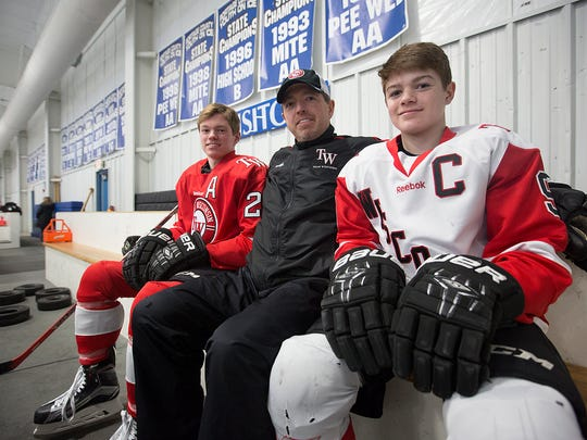 Paul Caufield, center, sits on the bench with his sons Brock, left, and Cole, right, at Ice Hawks Arena in Stevens Point, Thursday, Feb. 25, 2016. Paul Caufield is the all-time career scoring leader in UWSP hockey history, while both his sons have committed to play hockey at the Ohio State University.