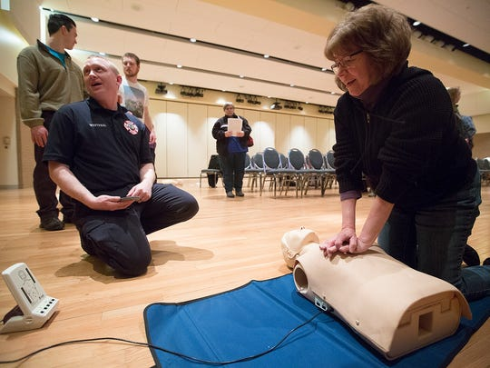 Roxanne Erickson of Medford, right, practices CPR under the supervision of firefighter/paramedic Shane Westphal, left, during training in the Melvin Laird Room at the University of Wisconsin - Stevens Point on Wednesday.