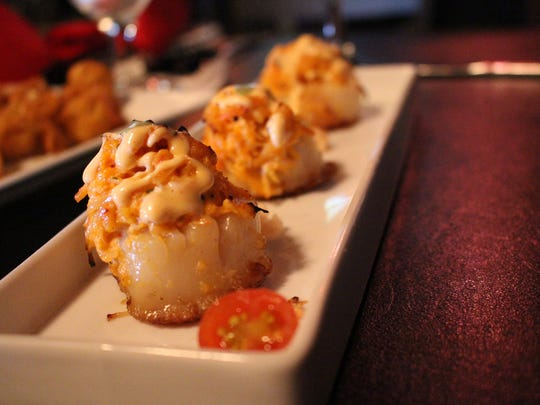 """Perfectly seared scallops are topped with a spicy crab and shrimp blend for the """"Scallop Volcano"""" appetizer."""