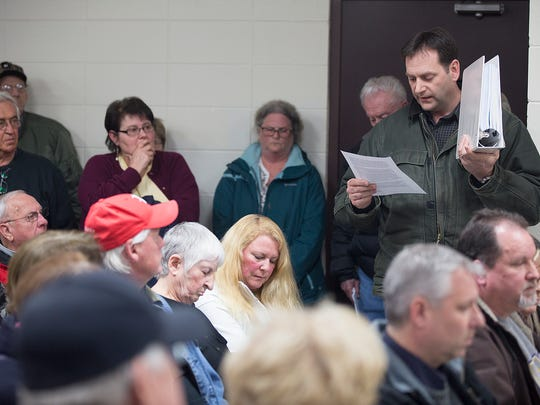 Former Port Edwards Village Administrator Joe Terry holds up public documents that he received from the Greenfield Police Department and Port Edwards officials regarding the hiring of two Greenfield police officers during public comment at a meeting of the Protective Services Committee at Edwards Alexander Shelter in Port Edwards, Tuesday, March 1, 2016.