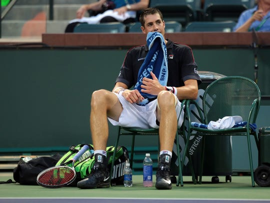 American John Isner takes a moment between games while
