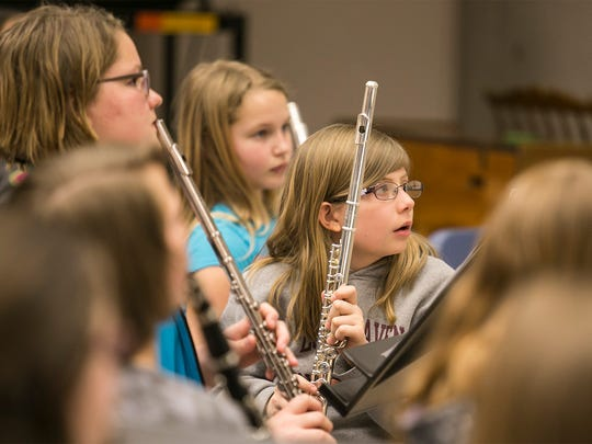 "Fifth-grade flute players Kendall Brooks, left, and Caitlynn Hilt give their attention to award-winning composer and conductor Brian Balmages Wednesday, March 16, 2016, at Spring Grove Intermediate School. The fifth- and sixth-grade band, will play ""Tears of Arizona"" publicly for the first time during a concert, held at the school on March 31, and then again in Washington D.C in May. Amanda J. Cain photo"