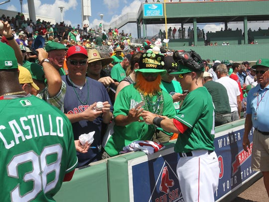 Red Sox All-Star Brock Holt signs an autograph for Arthur Desmarais at JetBlue Park on Thursday, St. Patrick's Day. Wearing green on St. Paddy's Day is tradition, especially of you're attending a Boston Red Sox game.