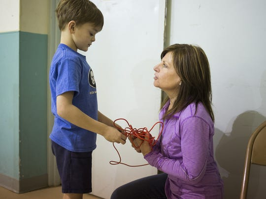 Ian Torbert, 7, gets a jump rope from Marcy Laferte. More than 80 children play games, socialize and listen to a presentation on positive living during an evening at the Peach Bottom Recreation Center in Delta, Thursday, March 24, 2016.
