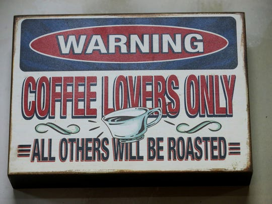 A sign that hangs next to the coffee bean roaster at Just Love Coffee Roasters on Tuesday, March 29, 2016
