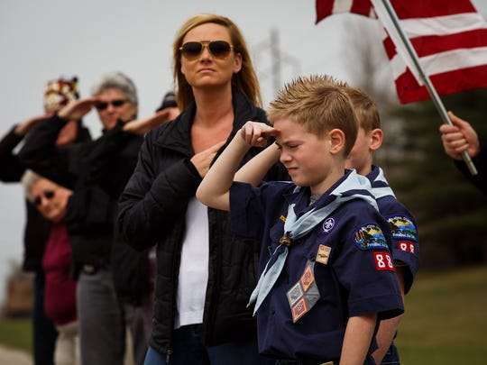 Boy Scouts salute as the motorcade for Officer Susan Farrell makes its way to Highland Memorial Gardens Cemetery in Des Moines on Wednesday, March 30, 2016. Farrell was one of the officers killed in a car crash early Saturday morning on Interstate 80.