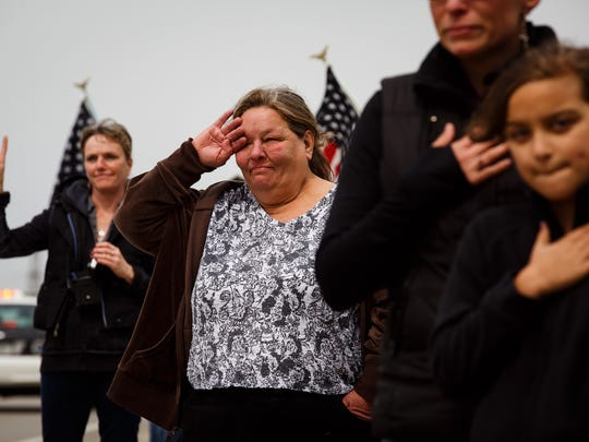 Nancy May, of Des Moines, wipes away a tear as the motorcade for Officer Susan Farrell makes its way to Highland Memorial Gardens Cemetery in Des Moines on Wednesday, March 30, 2016. Farrell was one of the officers killed in a car crash early Saturday morning on Interstate 80.