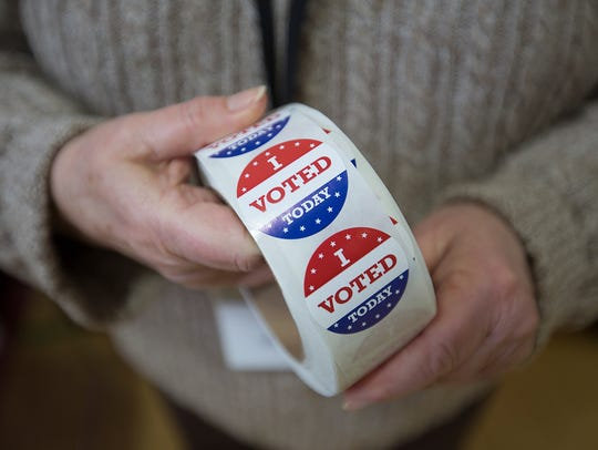 "An election worker hands out ""I Voted Today"" stickers."