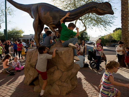Kids play on a dinosaur statue while waiting to enter
