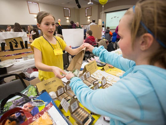 Carolyn Heuss, 11, of Antigo, left, sells Abby Sterken,