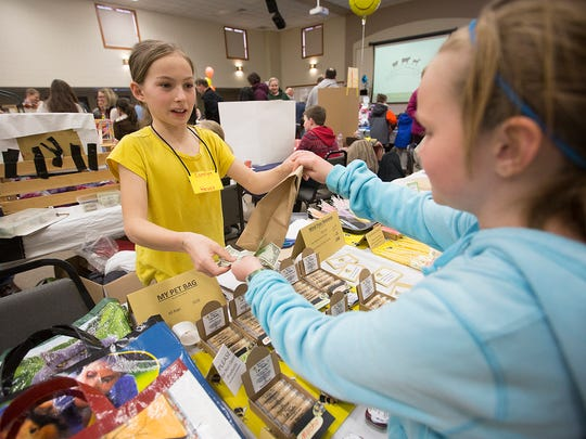 Carolyn Heuss, 11, of Antigo, left, sells Abby Sterken, 11, of Wausau items from her booth, Mind Your Beeswax, at the Kids Awesome Business Fair at Mount Olive Lutheran Church in Weston, Friday, April 8, 2016. Heuss's booth sold a variety of lip balm and candles.