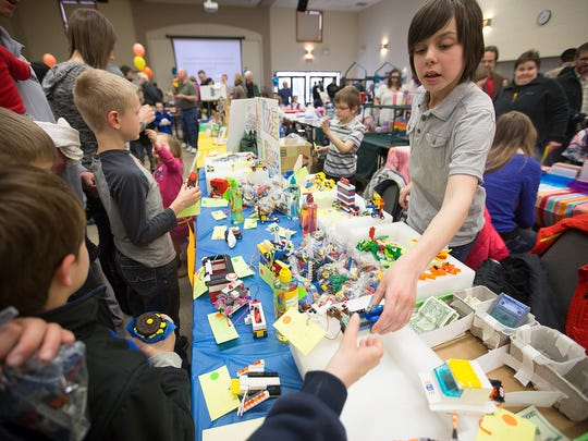Axel Mahler, 11, of Merrill, right, helps a customer at his booth, All Kinds of Legos, during the Kids Awesome Business Fair at Mount Olive Lutheran Church in Weston, Friday, April 8, 2016.
