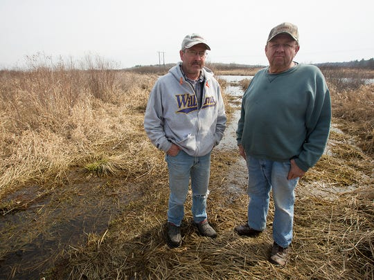 Bob Duda of Linwood, left, and Gary Konop of Linwood, right, stand on part of  Konop's land that has been flooded because of an embankment on William Stack's property, Tuesday, March 22, 2016. Stack added an embankment to preserve the marsh land on the property. Neighbors and farmers allege that the embankment has caused flooding and crop damage.