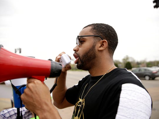 Community activist Derris Ross speaks to protestors