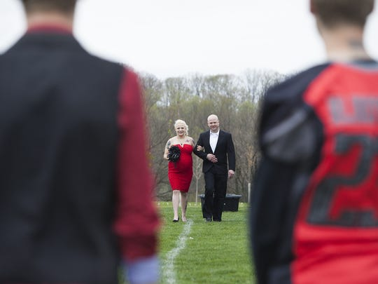 Beth Ford is walked onto the field by her brother Joseph Ford. Cody Klinefelter, 25, and Beth Ford, 36, are married before friends, family and Cody's Hanover Rhinos football teammates at Manheim Adventure Park in Glenville prior to a Rhinos' game, Saturday, April 23, 2016.