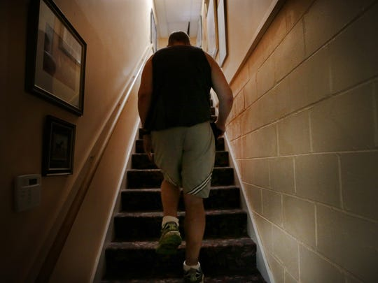 "John Miller walks up the stairs from the basement of Charlie Browns Pancake & Steak House on April 15, 2016. Elizabeth Glover, owner of the Speedway restaurant, allowed Miller to live in the basement while he was wheelchair bound and recovering from an accident that turned his legs into ""sawdust."" The basement was accessible by an elevator."