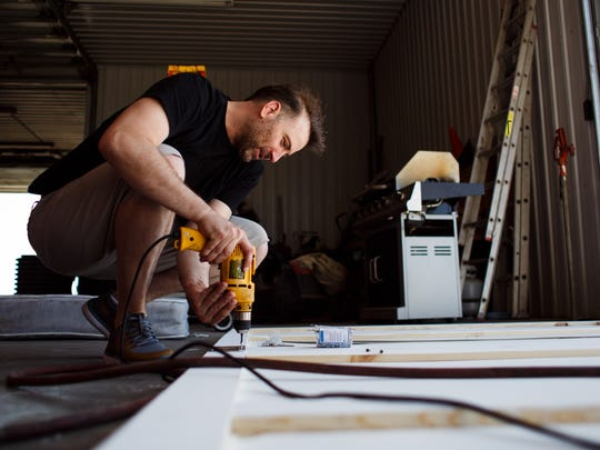 Chris Ihle installs hinges on the back of  a pop up
