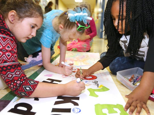 Catherine Lephew's second-graders at Hobgood Elementary, including, from left, Jamie Carlson, Emmaline Beckett and DeNyia Hayomon, work on a banner to celebrate every student in class getting to the next grade.