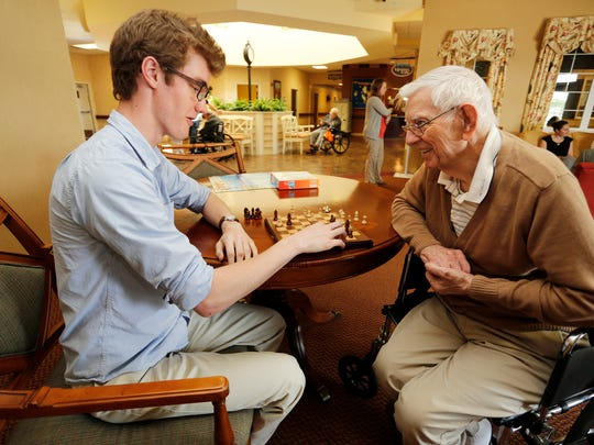 Bill Nangle, 89, right, smiles as he plays a game of