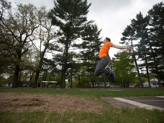 Port Edwards' Austin Hildebrandt triple jumps during practice at John Edwards High School, Thursday, May 12, 2016. Hildebrandt recently broke the school's triple jump record which was previously held by his older brother.