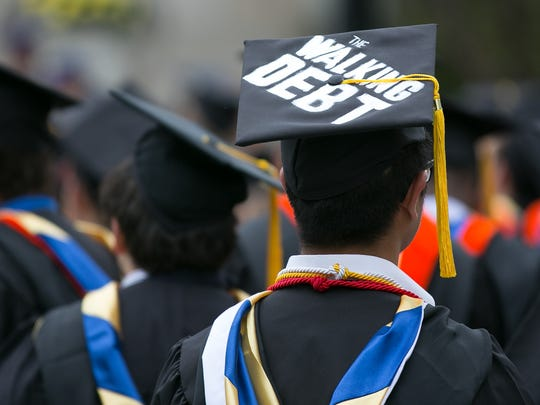 """George Iwaoka of Cliffside Park, New Jersey, wears a cap that says """"The Walking Debt"""" at the University of Rochester's Commencement ceremony in Rochester on Sunday, May 15, 2016."""