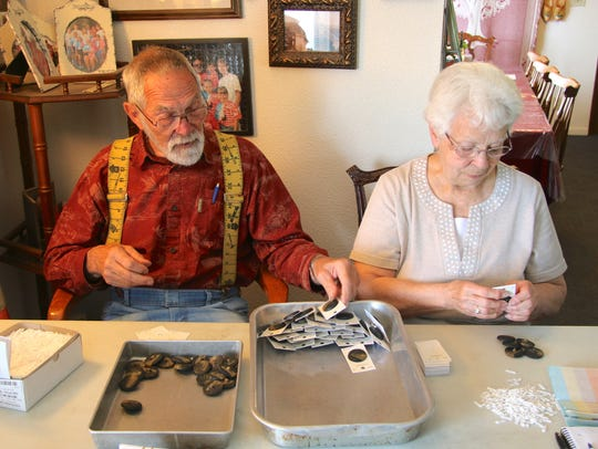 Gary and Karen Galema attach buttons to cards in their