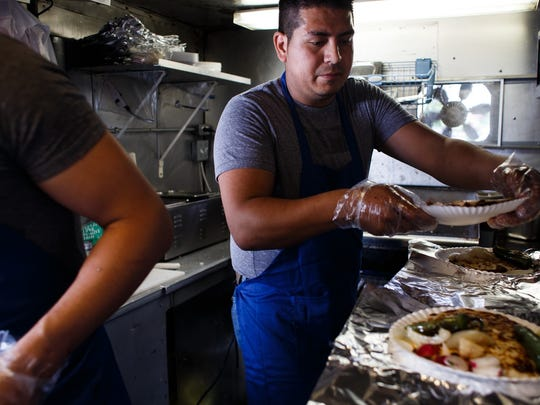 Antonio Ayala Zarate prepares a lunch plate at his brother Itzama Ayala Zarate's Taco Truck, Taqueria Express, in Des Moines on Tuesday, May 17, 2016. The City of Des Moines is planning to pass more rules to govern the neighborhood taco trucks outside of the downtown food truck program, specifically giving them a 10:30 pm mandatory close time, while downtown trucks can operate until 1:30am.