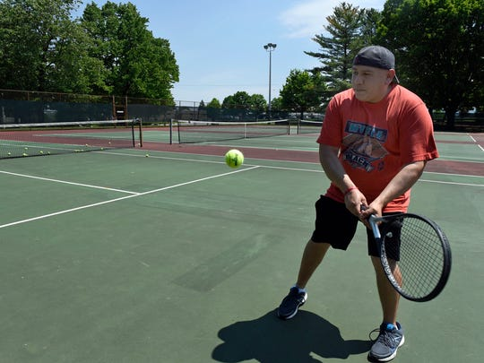 Jose Flores plays tennis at Chambersburg Memorial Park. The replacement of the courts is among the projects included in a list to be paid for by a $9.75 million bond issue approved by borough council Monday.
