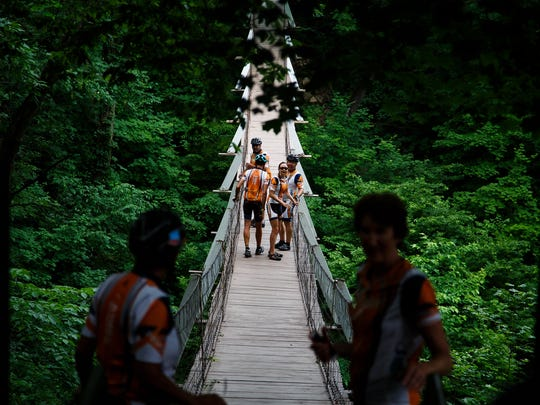Members of the RAGBRAI preride team including Scott Garner, back left, Randy Hecht, left, Andrea Parrott, front right, and TJ Juskiewicz walk along the swinging bridge in Columbus Junction on Saturday, June 11, 2016.