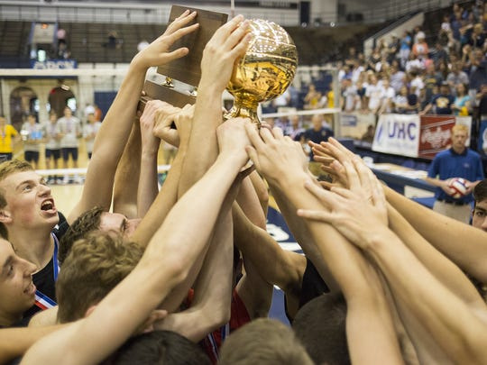 Hempfield's swarms the championship trophy. Hempfield defeats Penn Manor 3-2 to win the PIAA Class AAA boys' volleyball state championship title at Penn State University's Rec Hall in State College, Saturday, June 11, 2016.