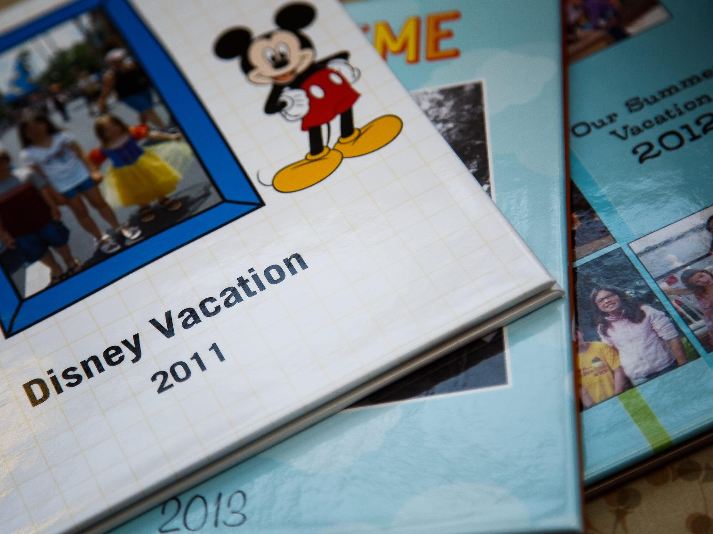 Photo books documenting family vacations are on display