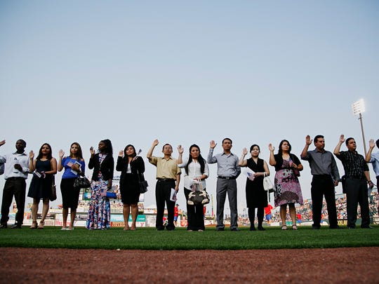 U.S. District Judge Robert W. Pratt, Southern District of Iowa, presides over a naturalization ceremony at Principal Park and administers the Oath of Allegiance to 30 new United States citizens from 14 different countries in Des Moines on Friday, July 3, 2015.