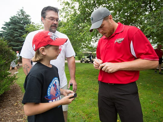 San Jose Sharks captain and Plover native Joe Pavelski signs a hockey puck for Hayden Miller, 10, of Stevens Point, left, and his father, Darren Miller of Stevens Point, center, during the Joe Pavelski Charity Golf Tournament at the Stevens Point Country Club, Thursday, June 23, 2016.