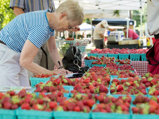 Margaret Webster of Ithaca, buys strawberries and raspberries Tuesday morning from the Reisinger's Apple Country stand at the Downtown Ithaca Farmers Market in Ithaca.
