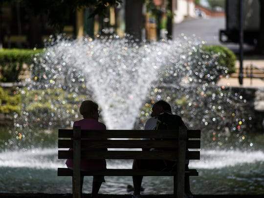 A couple enjoys time in the shade by the fountain at