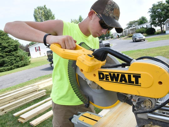 Luke Ritz, 17, cuts wood while building a new porch and ramp at a Shippensburg mobile home on Tuesday, July 12, 2106.