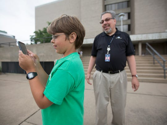 Mark Phillippi of Stevens Point watches as his son Alex Phillippi, 11, plays Pokemon Go at the Sundial at the University of Wisconsin - Stevens Point, Thursday, July 14, 2016.
