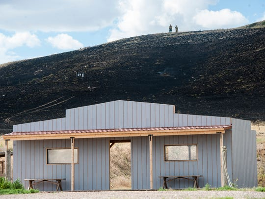 Firefighters observe damage from a grass fire at the