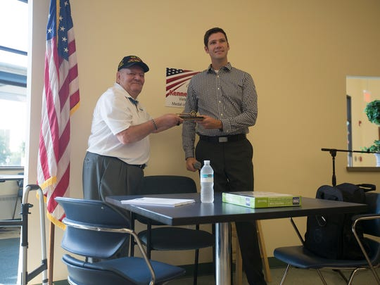 Mayor Zach Vruwink gives Vietnam War veteran and Medal of Honor recipient Ken Stumpf a key to the city during the American Heroes Cafe at the Lowell Senior Center on Wednesday in Wisconsin Rapids.